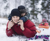 Portrait of happy father with his son outside with snowman — Stock Photo
