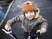 Little cute boy on bicycle smiling close up — Stock Photo