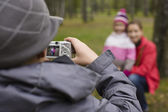 Little offspring shooting his family in park — Stock Photo