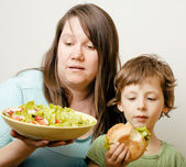 Fat woman holding salad and little cute boy with hamburger teasing — Stock Photo