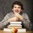 The young emotional student with the books and red apple in class room, at blackboard — Stock Photo #37420549
