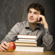 The young emotional student with the books and red apple in class room, at blackboard — Stock Photo #37420555