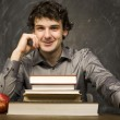 The young emotional student with the books and red apple in class room, at blackboard — Stock Photo #37420561