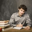 The young emotional student with the books and red apple in class room, at blackboard — Stock Photo #37420563