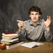 The young emotional student with the books and red apple in class room, at blackboard — Stock Photo #37420573