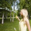 Beauty blond wommaking bubbles outside — Stock Photo #37421043