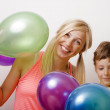 Pretty family with color balloons on white background, blond woman with little boy — Stock Photo #37421415