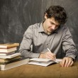 Stock Photo: Young emotional student with books and red apple in class room