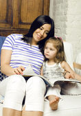 Portrait of mother and daughter reading — Stock Photo