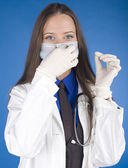 Portrait of young pretty doctor with stethoscope in mask and gloves — Stock Photo