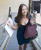 Portrait of pretty young woman with bags in the shop — Stock Photo