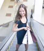 Portrait of pretty young woman with bags in the shop — Stockfoto