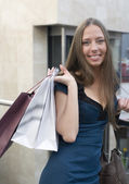Portrait of pretty young woman with bags in the shop — Stok fotoğraf