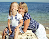 Portrait of young family having fun on the beach, mother and daughter at sea — Stock Photo