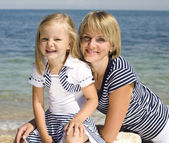 Portrait of young family having fun on the beach, mother and daughter at sea — Stockfoto