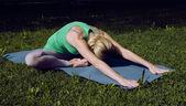 Blonde girl doing yoga in park — ストック写真