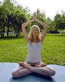 Ragazza bionda facendo yoga nel parco — Foto Stock