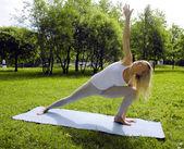 Blonde girl doing yoga in park — Stockfoto