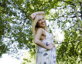 Happy blond young woman in park smiling — Stock Photo