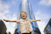 Little cute boy standing near business building, smiling — Stock Photo