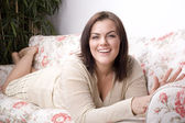 Portrait of pretty young woman smiling laying on sofa — Stock Photo
