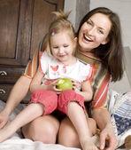 Ritratto di felice madre e figlia nel letto, sorridendo abbracciarsi, tenendo la mela verde — Foto Stock