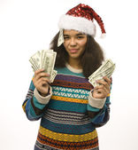 Cute young girl in santas red hat with money — Stockfoto