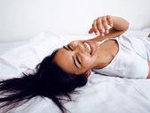 Pretty brunette in bed smiling flirting — Stock Photo