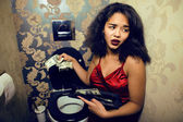 Pretty young woman in restroom with money — Stock Photo