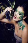 Woman with creative make up like snake with rat in her hands — Foto de Stock