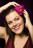 Portrait of beauty brunette woman with flower in her hair — Stock Photo
