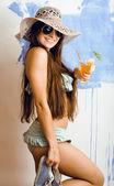 Cute bright woman in sunglasses and hat with cocktail in bikini in studio — Stock Photo