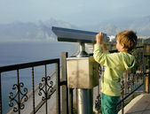Little cute boy looking through telescope at sea viewpoint — Stock Photo
