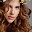 Beauty young woman with flowers in curly hair and make up — Stock Photo