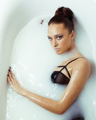 Beauty young brunette girl in bath, taking milk spa — Stock Photo