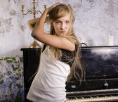 Young blond girl playing on piano — Stock Photo