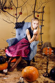 Blond cute girl in halloween interior — Stock Photo