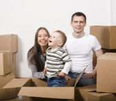 Stock-photo-smiling -family-in-new-hous e-playing-with-boxe s — ストック写真