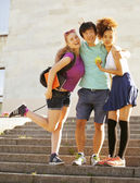 Cute group of teenages at the building of university with books huggings — Stock Photo