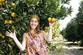 Pretty woman in orange grove smiling — Stockfoto