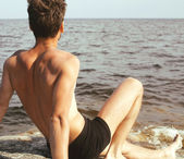 Handsome young man at beach — Stock Photo