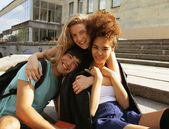 Cute group teenages at the building of university with books huggings — Stock Photo
