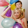 Pretty family with color balloons on white background, blond woman with little boy on birthday party — Stock Photo #51421517