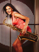 Young pretty woman with saxophone — Stock Photo