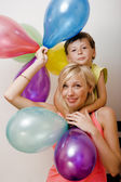 Pretty family with color balloons on white background, blond woman with little boy on birthday party — Stock Photo