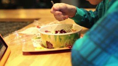 мальчик ест салат в ресторане быстрого питания — Стоковое видео
