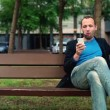 Man eating apple with smartphone — Stock Video