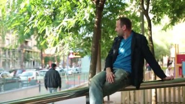 Relaxed man sitting on handrail — Vidéo