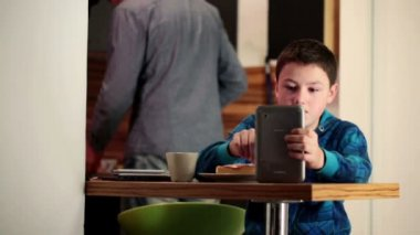 Boy using tablet during breakfast — Stock Video