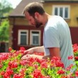 Stock Video: Man checking flowers on balcony